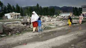 Pakistanis walk past the rubble of the demolished compound of slain al-Qaida leader Osama bin Laden in the northern town of Abbottabad this week. Bin L