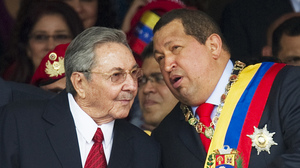 Venezuelan President Hugo Chavez (right) speaks with his Cuban counterpart, Raul Castro, during a military parade earlier this year in Caracas, Venezuela. Chavez has provided an economic lifeline to Cuba. Now, that lifeline is under threat as the Venezuelan leader fights cancer and faces re-election.
