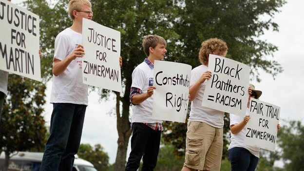 People hold signs during a small April rally in Sanford, Fla., that was billed as an opportunity to show support for the constitutional rights of George Zimmerman and Trayvon Martin.