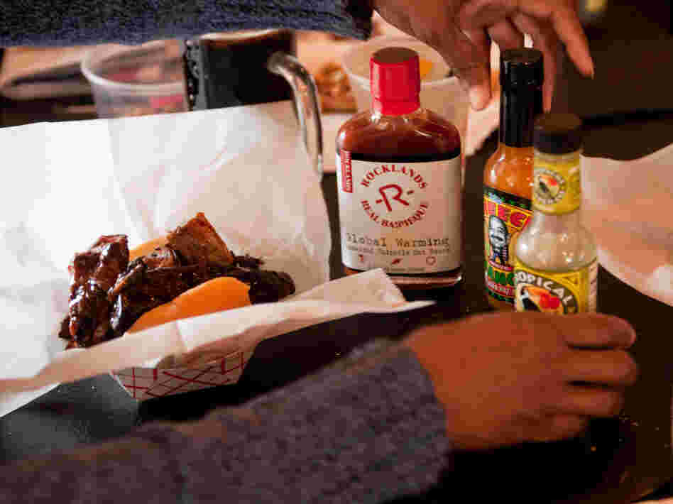 Tami Franklin tries a variety of hot sauces on her barbecue ribs at Rocklands Barbeque and Grilling Company in Arlington, Va.