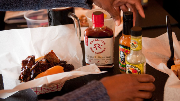 Tami Franklin tries a variety of hot sauces on her barbecue ribs at Rocklands Barbeque and Grilling Company in Arlington, Va. (NPR)