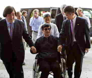 Chinese activist Chen Guangcheng (in wheelchair) held the hand of Gary Locke (at right) the U.S. ambassador to China in Beijing as he arrived at a hospital in Beijing on Wednesday.