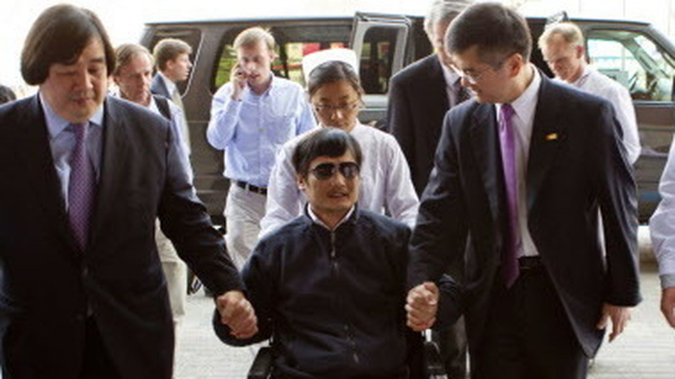 Chinese activist Chen Guangcheng (in wheelchair) held the hand of Gary Locke (at right) the U.S. ambassador to China in Beijing as he arrived at a hospital in Beijing on Wednesday. (AFP/Getty Images)
