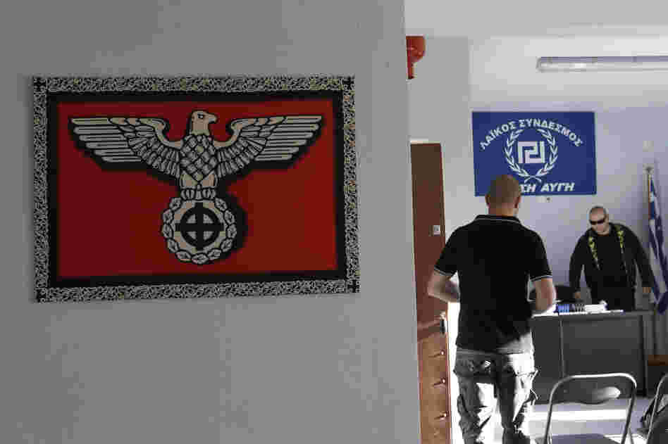 A Nazi-style poster with a Celtic cross replacing the swastika is displayed on the wall as Golden Dawn candidate Giorgos Germanis (right) and an unidentified man are seen at a party office in the suburban town of Artemis, east of Athens.