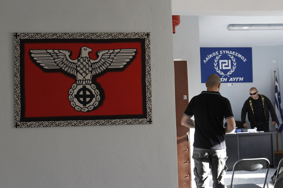 A Nazi-style poster with a Celtic cross replacing the swastika is displayed on the wall as Golden Dawn candidate Giorgos Germanis (right) and an unidentified man are seen at a party office in the suburban town of Artemis, east of Athens. (AP)