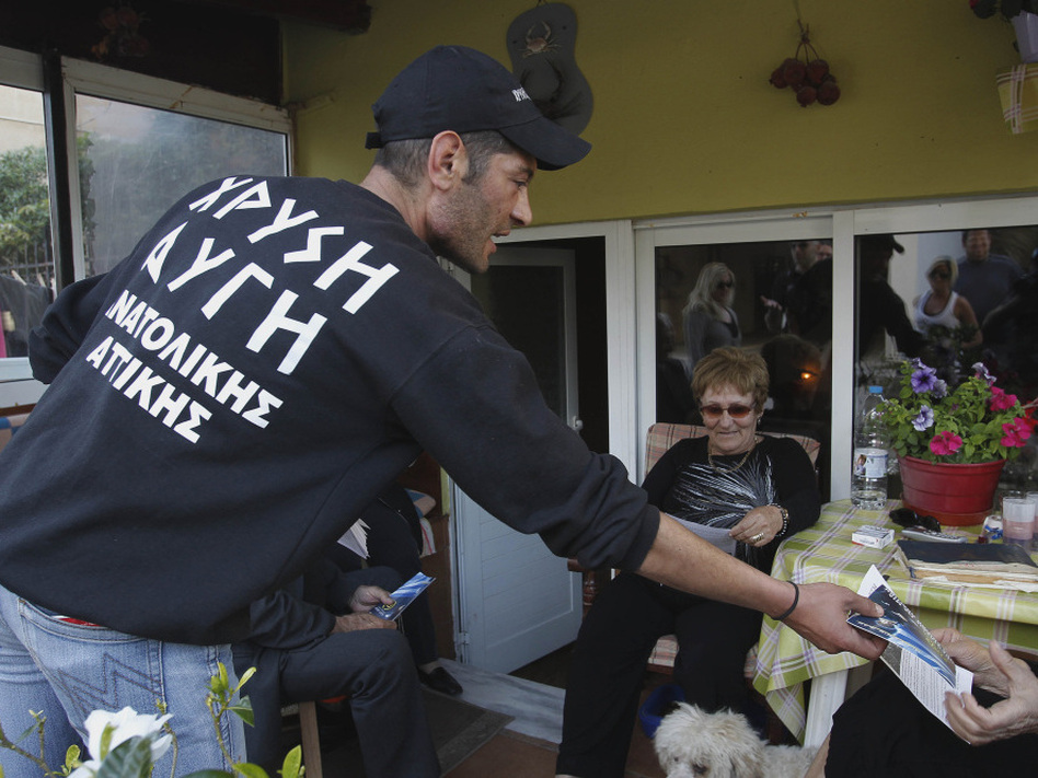 Reeling from a vicious financial crisis that has cost them pensions and jobs, Greeks have been turning away in droves from the mainstream politicians they feel have let them down. Here, a member of the far-right Golden Dawn party hands out election pamphlets in Artemis on April 26. (AP)