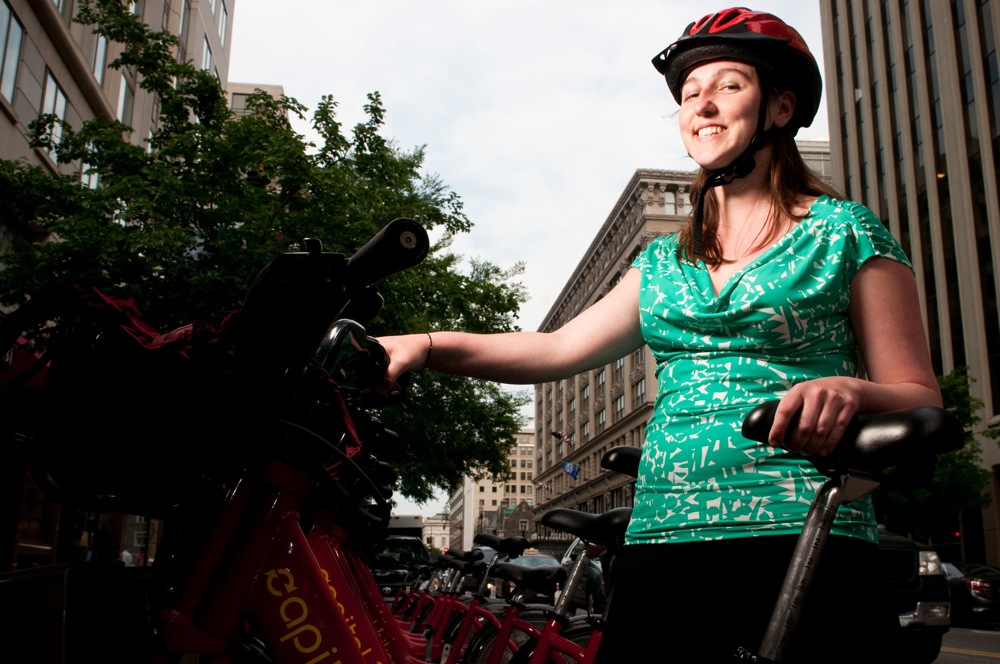"""Kay McLaughlin, an editorial coordinator, sports a Capital Bikeshare-branded helmet. """"This is my D.C. helmet. I keep it on top of my desk,"""" she says. She has a second helmet for riding at home."""