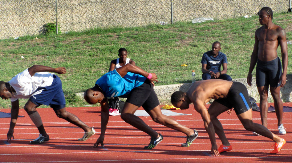 Top Jamaican sprinters, including Olympic gold medalist Asafa Powell (in blue), practice at Kingston's National Stadium on one of the country's few synthetic tracks. (NPR)