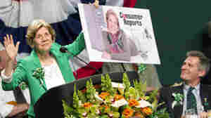 Democratic Senate candidate Elizabeth Warren holds up a poster of herself as Sen. Scott Brown, R-Mass., looks on during the annual St. Patrick's Day Breakfast in Boston on March 18. A civility pledge between the candidates has kept attack ads largely on the sidelines in their race.
