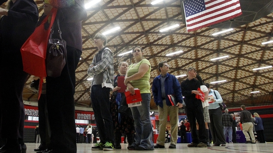 People wait in a line at a job fair on April 10, 2012, in Gresham, Ore. Employment grew by 115,000 last month, but the unemployment rate dip was likely due to people leaving the workforce rather than people getting hired, analysts say. (AP)