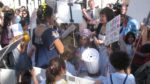 """Moms and their kids protest a proposed ban on homemade food at bake sales in New York City schools at a rally near City Hall in 2010. One sign read, """"I wanna get obese on my terms. No junk food."""" (Flickr)"""