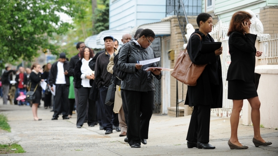 People seeking jobs wait in line to speak to employers at a career fair Thursday in the Queens borough of New York. (AFP/Getty Images)
