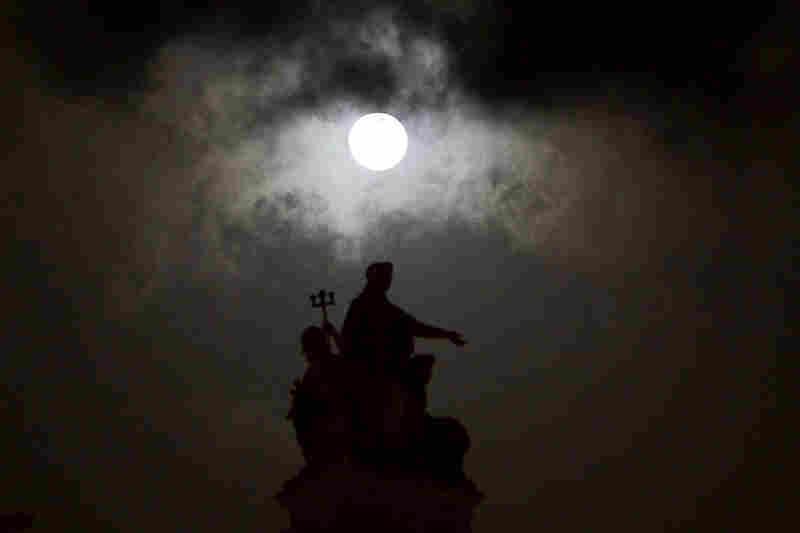 The moon is seen over the landmark Chhatrapati Shivaji Terminus in Mumbai, India, on Saturday.