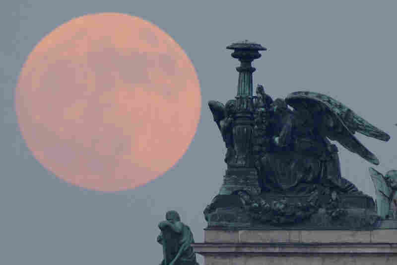 The full moon rises behind statues of angels fixed at the St. Isaak's Cathedral in St.Petersburg, Russia.
