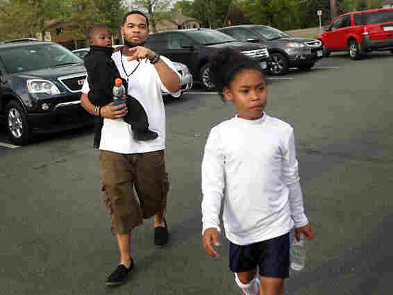 Joseph Arradondo walks with son Nasir, 2, and daughter Nevaeh, 9, before Nevaeh's soccer game.