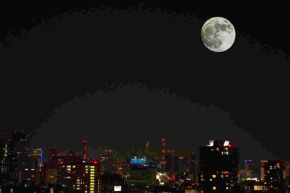 The moon shines bright over Tokyo, Japan.