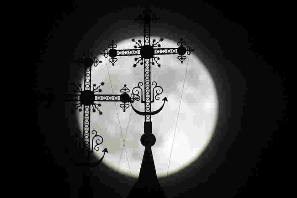 The full moon rises behind a steeple with crosses of an Orthodox church in the town of Novogrudok, Belarus.
