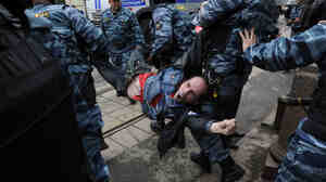 Police officers carry an anti-Putin protester, who was detained in central Moscow, on Monday.