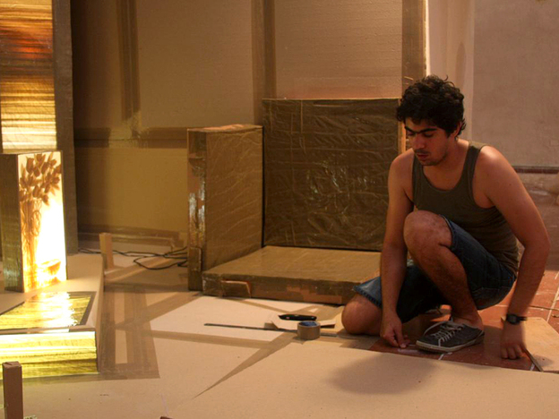 In a former prison cell, Cuban artist Oswaldo Gonzalez works on a piece he calls <em>Domestic Scene</em>. Built with cardboard, masking tape and paper, the work creates a living room atmosphere.