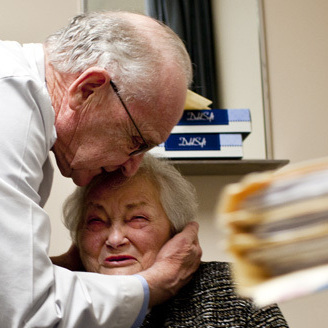 "AnnaBelle Bowers' long-time physician, Walter Watkin, gives her a kiss on the forehead at the end of her visit. When asked how long she had been coming to see him, he said, ""Long enough for her file to be 2 inches thick."""