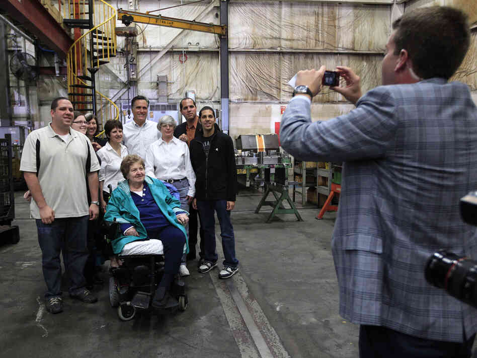 Mitt Romney poses with a group of supporters at a Euclid, OH town hall-style meeting where some voters didn't exactly help him keep to his themes.