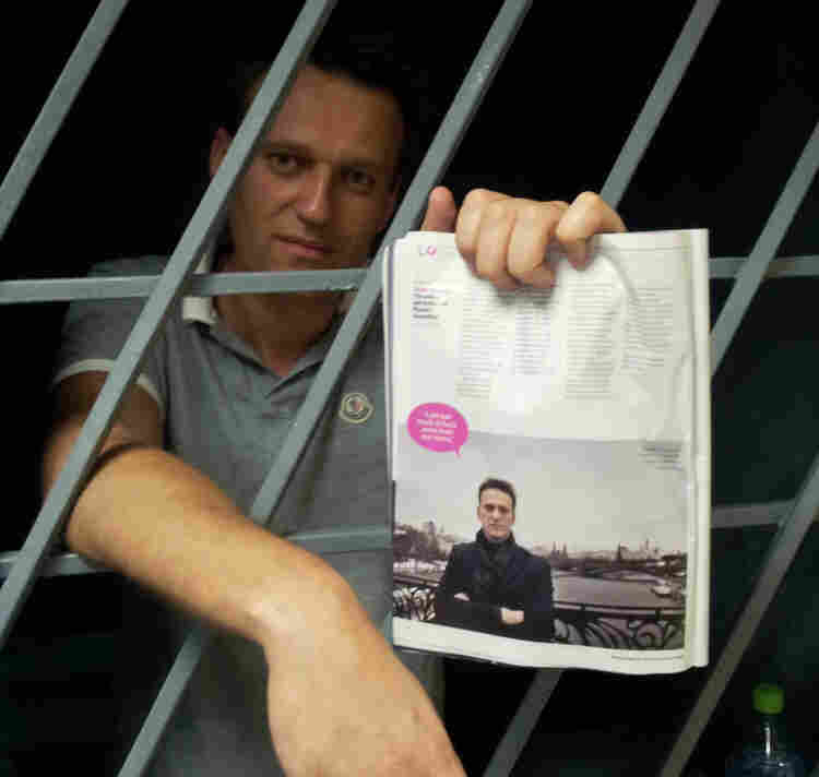 Alexei Navalny, a prominent anti-corruption whistleblower and blogger, holds an issue of Time Magazine, with his photograph, as he stands behind bars in a prison after he was detained in Moscow on Sunday.