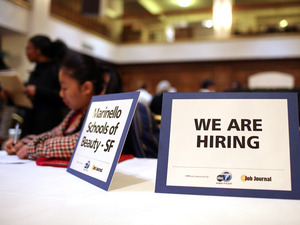 "A ""we are hiring"" sign is displayed on a table during a job fair in San Francisco."