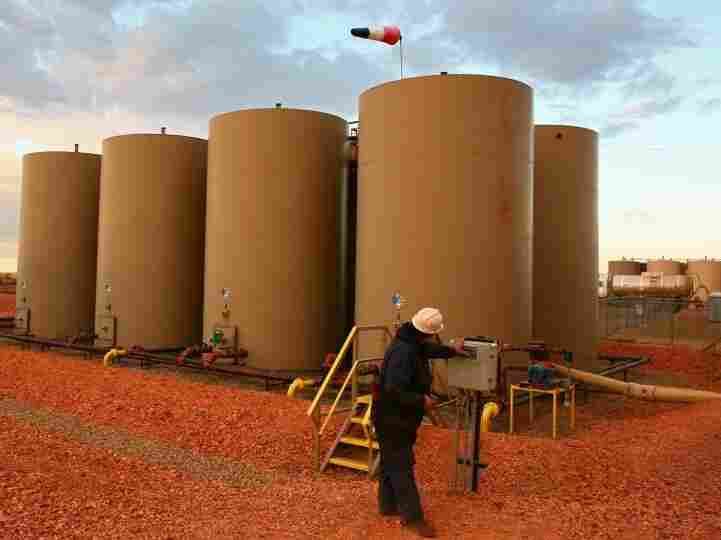U.S. oil production is at its highest level in decades. Here a worker transfers oil into a container tank outside Alexander, N.D., in October 2011.