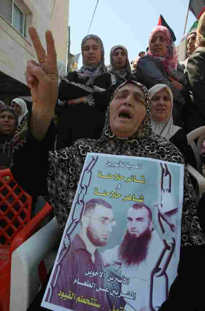 A Palestinian woman holds pictures of jailed relatives during a demonstration in the West Bank city of Hebron on Tuesday, May 8. Palestinians are protesting in solidarity with some 1,500 prisoners on hunger strike who are demanding an end to Israel's practice of detention without trial as well as more frequent family visits, among other issues.
