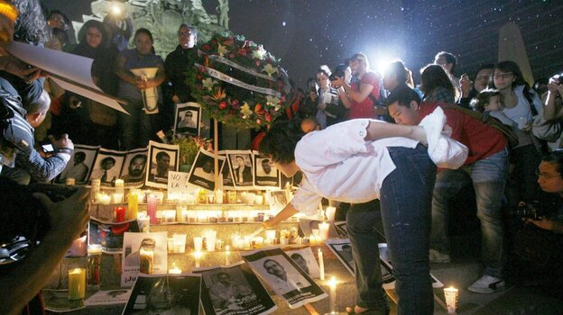 A woman lights a candle during a tribute to slain Mexican journalists at the Monument of Independence in Mexico City on