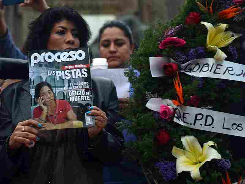 A mourner holds up a copy of Proceso magazine with investigative reporter Regina Martinez on its cover at the vigil in Mexico City last week. At the end of April, Martinez's body was found in her bathroom, beaten and strangled.