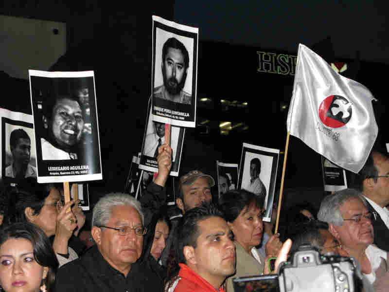 Mexicans hold up posters of journalists who have been killed in recent years, at a recent vigil in Mexico City.