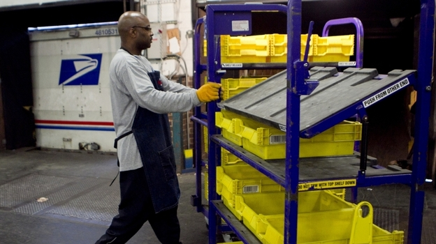 An employee loads flat trays onto a truck at the U.S. Postal Service processing and distribution center in Merrifield, Va. The USPS, which is projecting a $14.1 billion loss this fiscal year, is discussing restructuring options with potential advisers. (Bloomberg via Getty Images)