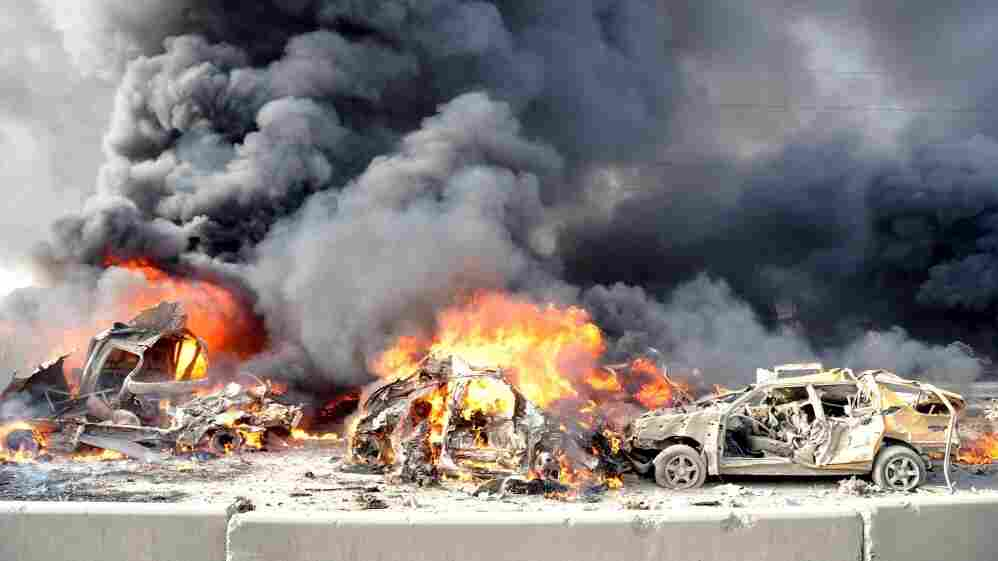 A pair of powerful bombs killed more than 50 people on the outskirts of Damascus on Thursday. This photo released by the official Syrian news agency SANA shows the aftermath. The blasts were the latest blow to a collapsing peace plan.
