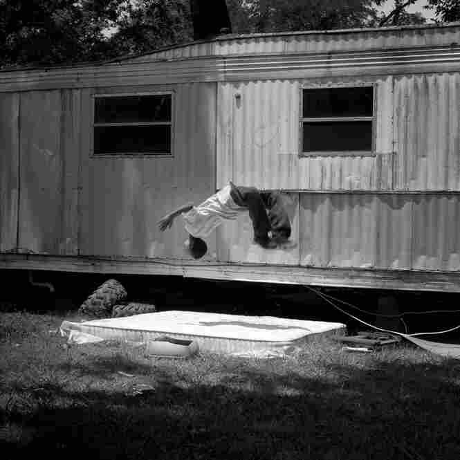 A young boy performs a back flip on a discarded mattress in his grandfather's backyard in Duncan, June 2011.