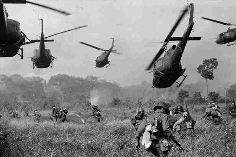 Hovering U.S. Army helicopters pour machine-gun fire into the tree line to cover the advance of South Vietnamese ground troops in an attack on the Viet Cong, March 1965.