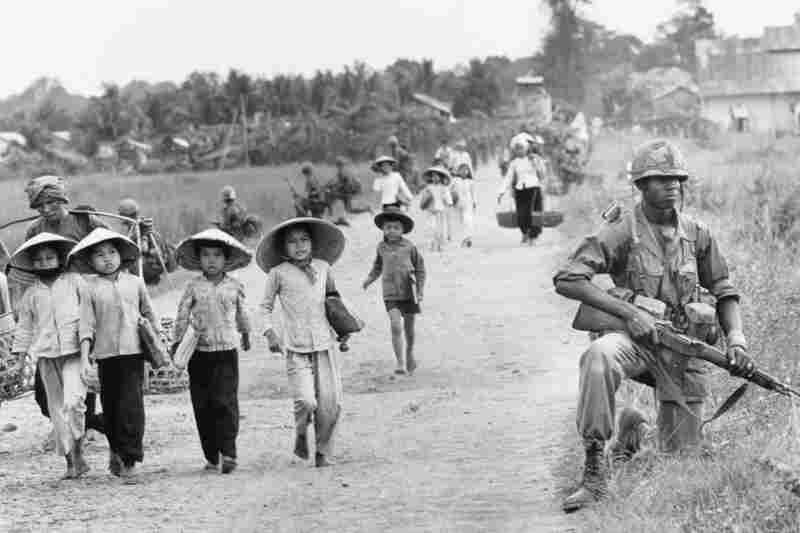 An American soldier guards the road as Vietnamese women and schoolchildren return home, December 1965.