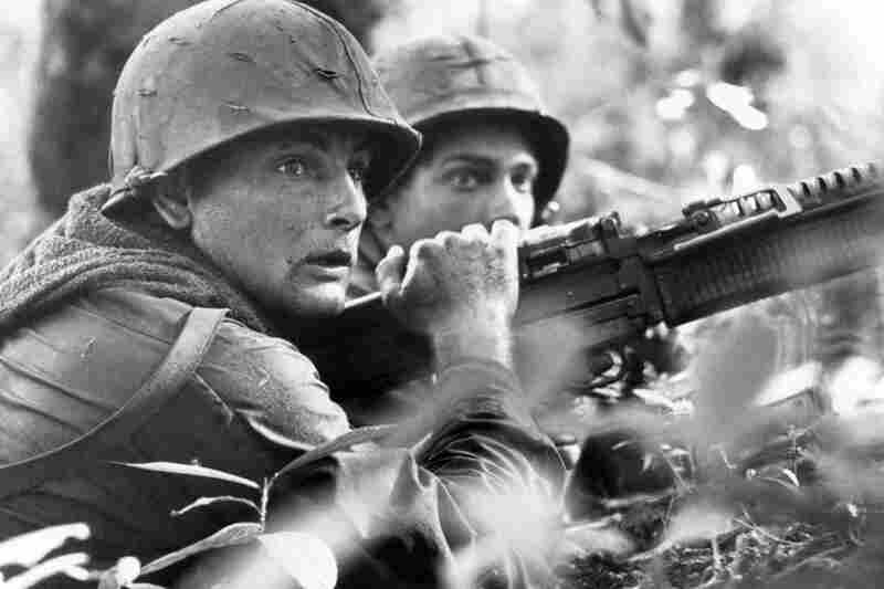 U.S. machine gunner Spc. 4 James R. Pointer (left) and Pfc. Herald Spracklen of Effingham, Ill., peer from the brush of an overgrown rubber plantation during a firefight, December 1967.
