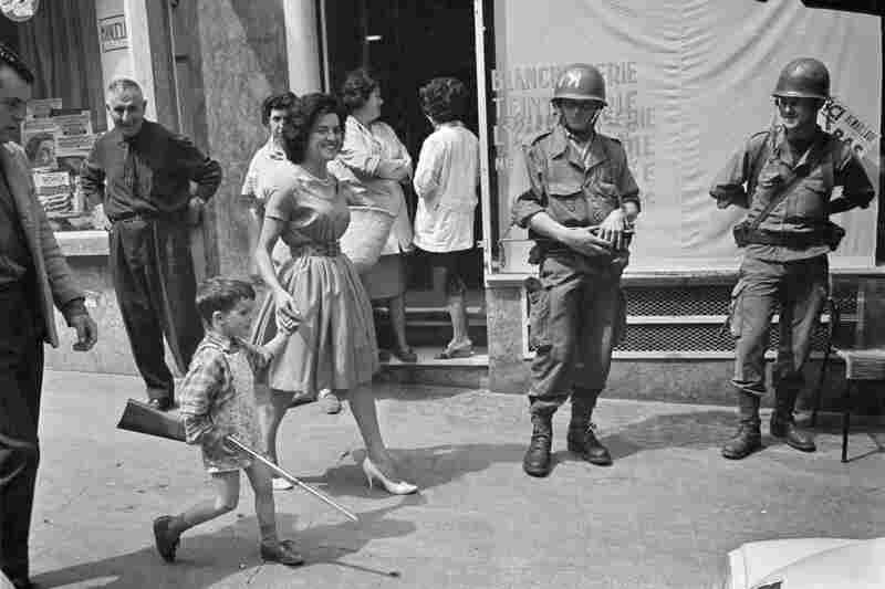 A boy carries a toy rifle past French soldiers at the Bastille Palace in Oran, Algeria, May 1962.