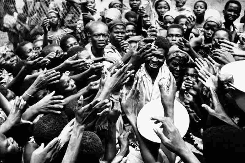 Scores of eager hands reach toward the Congolese official who distributes small rations of dried fish and palm oil to people at the hospital in Miabi, South Kasai, Congo, January 1961.