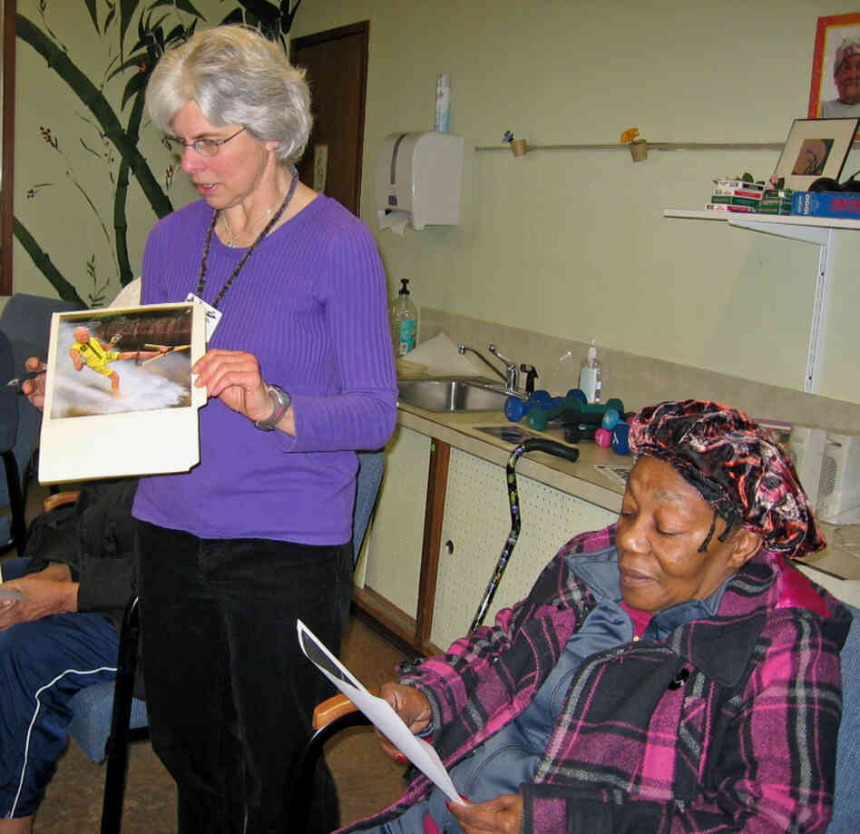 Linda White (left) leads a session based on a program called TimeSlips at a Seattle senior center. The idea is to show photos to people with memory loss to help them make up a story.