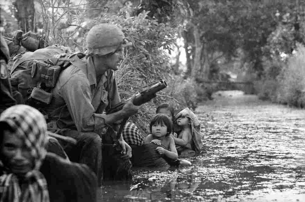 South Vietnamese children gaze at an American paratrooper as they cling to their mothers, hiding from Viet Cong sniper fire west of Saigon, January 1966.