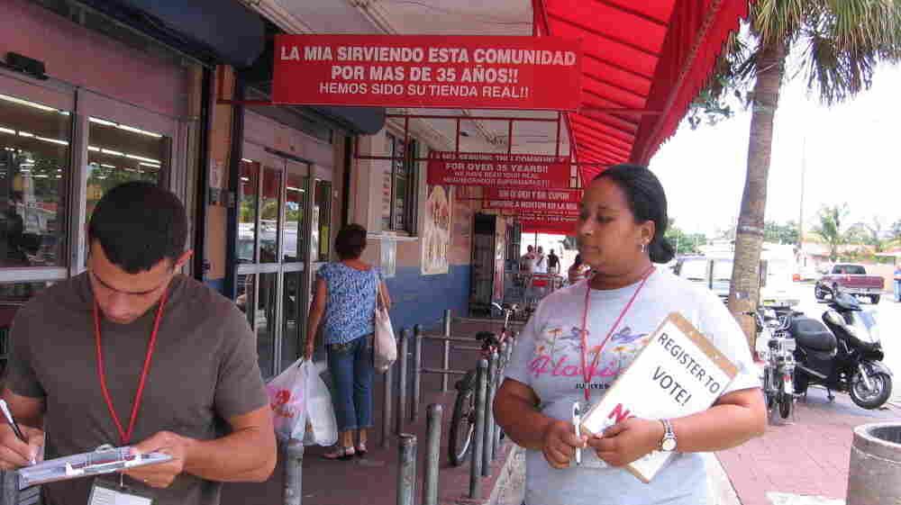 Melli Romero (right), a canvasser with the National Council of La Raza, works outside La Mia Supermarket in Miami on May 9.