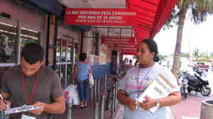 Melli Romero (right), a canvasser with the National Council of La Raza, works outside La Mia Supermarket in Miami on May 9.