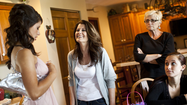 Kelley Hawkins (center) smiles at her daughter Carley (left) as her other daughter, Chelsea (right), looks on, in their family home in Harrisburg, Pa. (NPR)