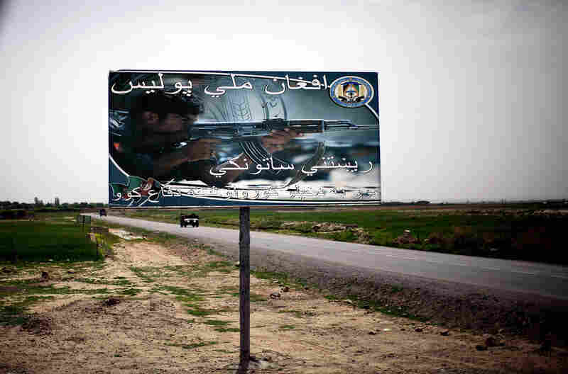 "A billboard reads ""Afghan National Police: The real guardian. We defend our own homes."" It sits next to one of the main roads leading in and out of an area where the local population supports the Taliban."