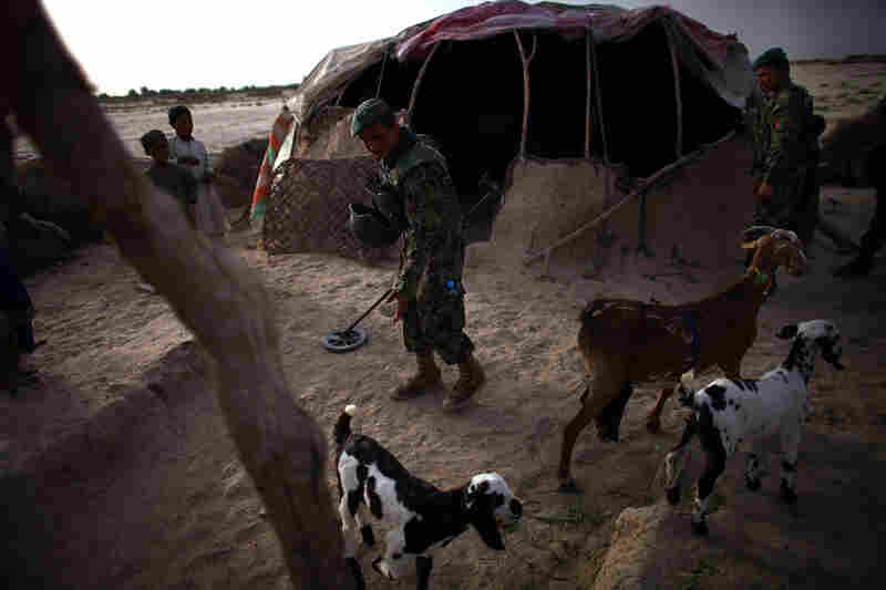 An Afghan soldier uses a metal detector while looking for bomb-making materials at house near Zangabad.