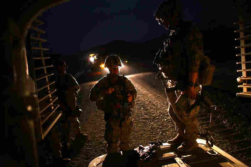 U.S. soldiers stand at the rear door to their armored vehicle after an all-day patrol with the Afghan National Army.