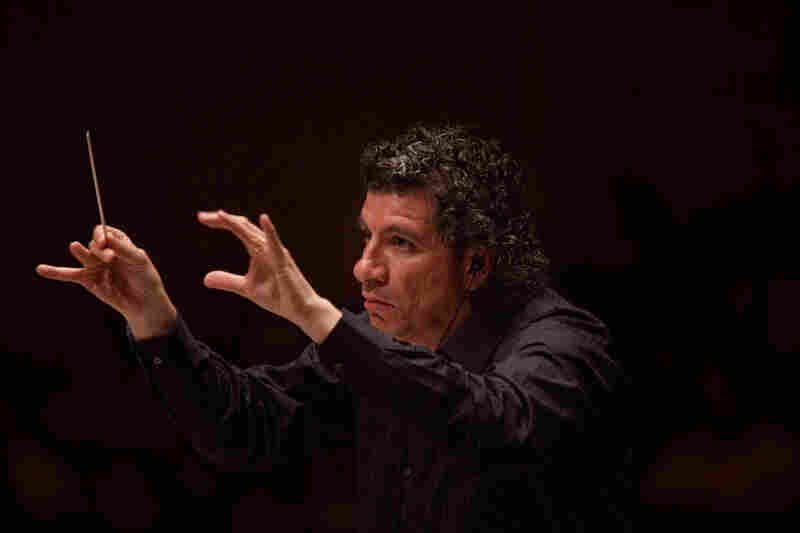 Like the other four conductors in Ives' massive symphony, music director Giancarlo Guerrero wears earbuds to hear the click track needed to keep all the musicians playing together.