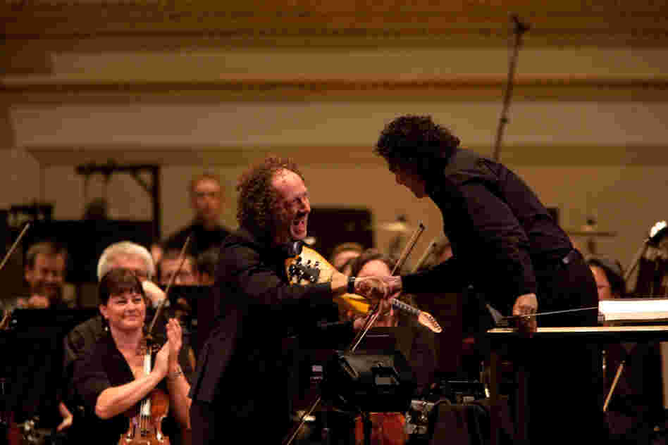 "Tracy Silverman shakes hands with conductor Giancarlo Guerrero. Silverman says Riley's concerto is ""a mashup of raga and ragtime."""
